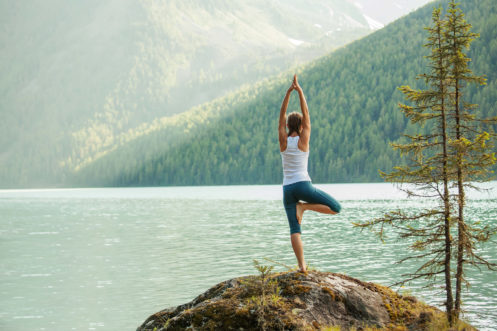 Woman Doing Yoga In Front Of A Lake