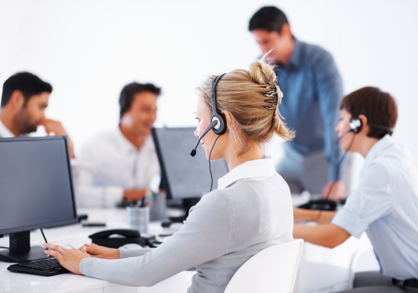 woman at screen with headphones and other workers