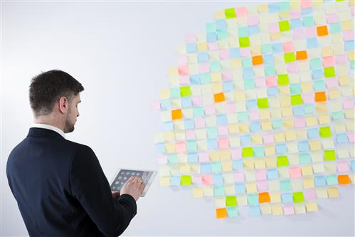 Business man standing with a wall full of sticky notes