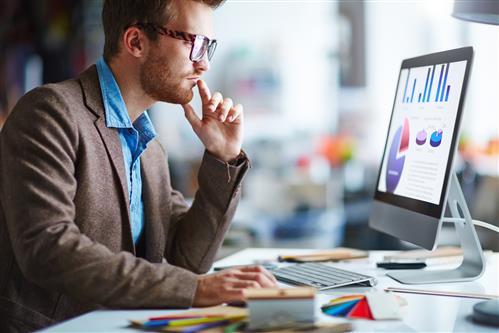 Young businessman at computer screen, thinking