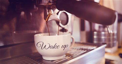 Coffee cup filling up labeled with words Wake Up