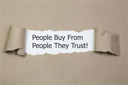 Torn strip of paper reveals quote - People Buy from People They Trust