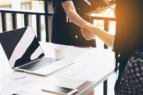 Two women shaking hands across a desk