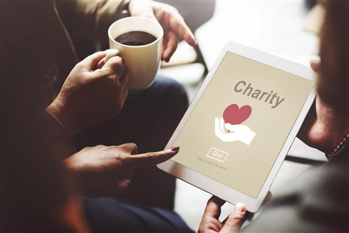 hands holding tablet with image of the red heart symbol under the word Charity