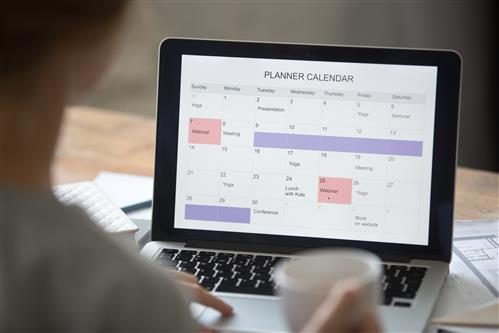Laptop screen showing planner calendar highlighted, corner of someone visible sitting at laptop