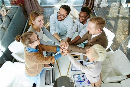 Young business group male and female sitting around meeting table, grasping hands in a huddle