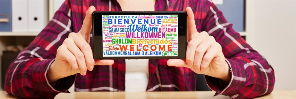 Hands holding smartphone horizontally with Welcome message in many languages