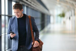 Young man walking through airport looking at his smartphone and smiling