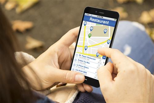 hands holding cell phone with local search map and listings for Restaurants on screen